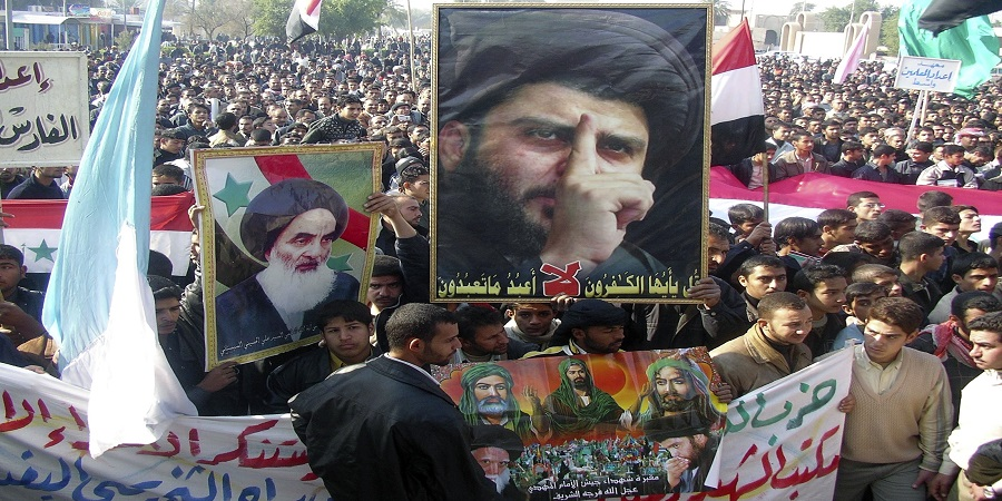 Protesters carry posters of Shi'ite cleric al-Sadr and Ayatollah al-Sistani during a demonstration against U.S. forces in Kut